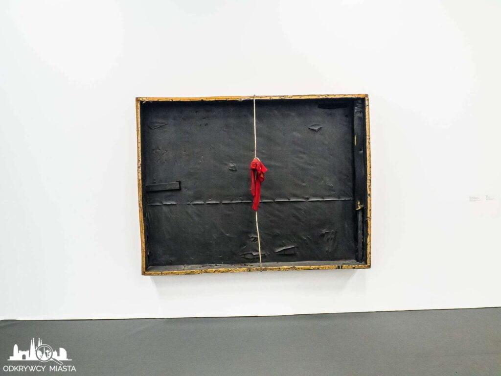 Antonio tapies obraz instalacja czarna skrzynka na ścianie z czerwoną apaszką