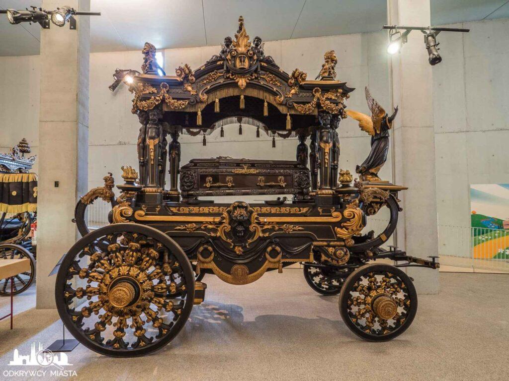Muzeum wozów pogrzebowych w Barcelonie czarny wóz ze złotymi zdobieniami i aniołem